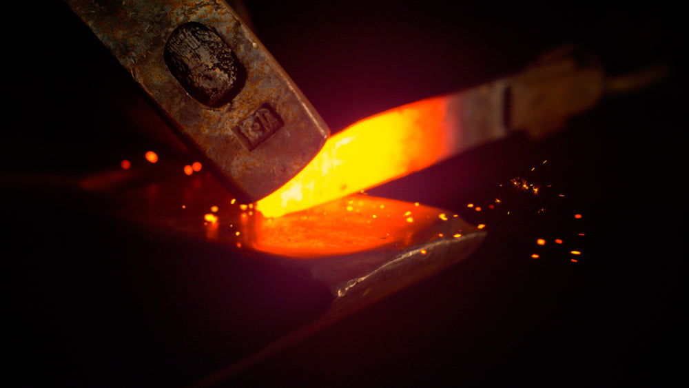 A steel knife being forged in by a blacksmith