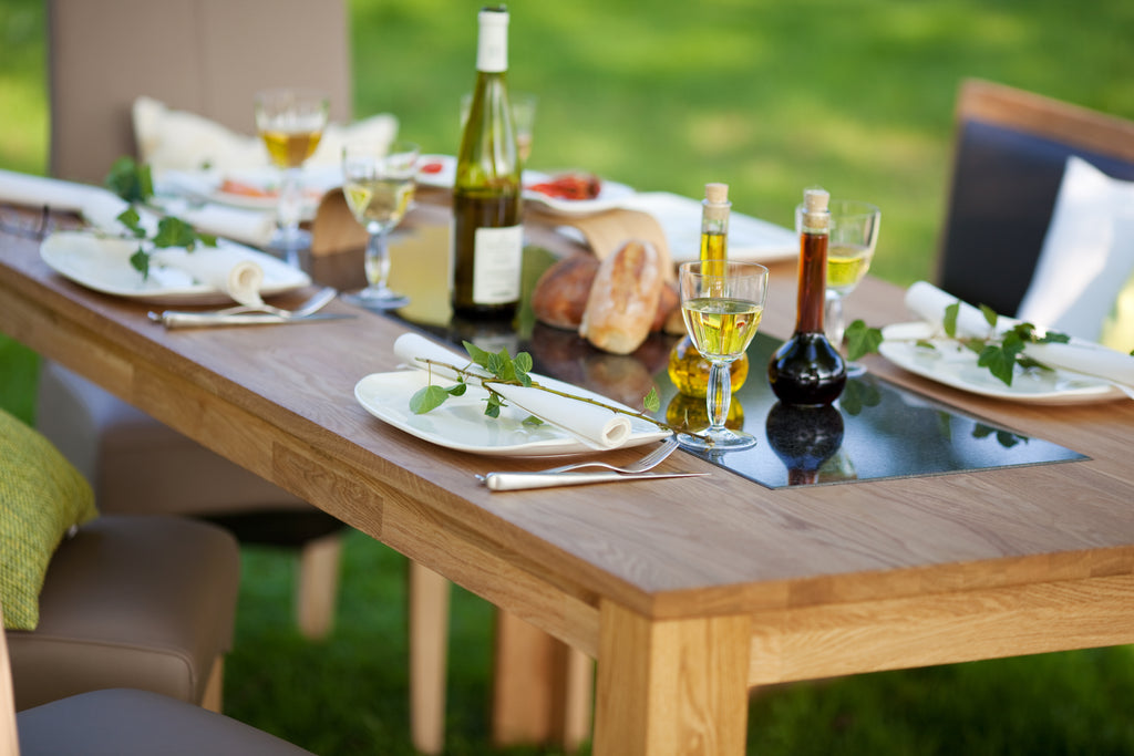 Outdoor wooden table on grass set for dinner with plates, wine glasses and drinks