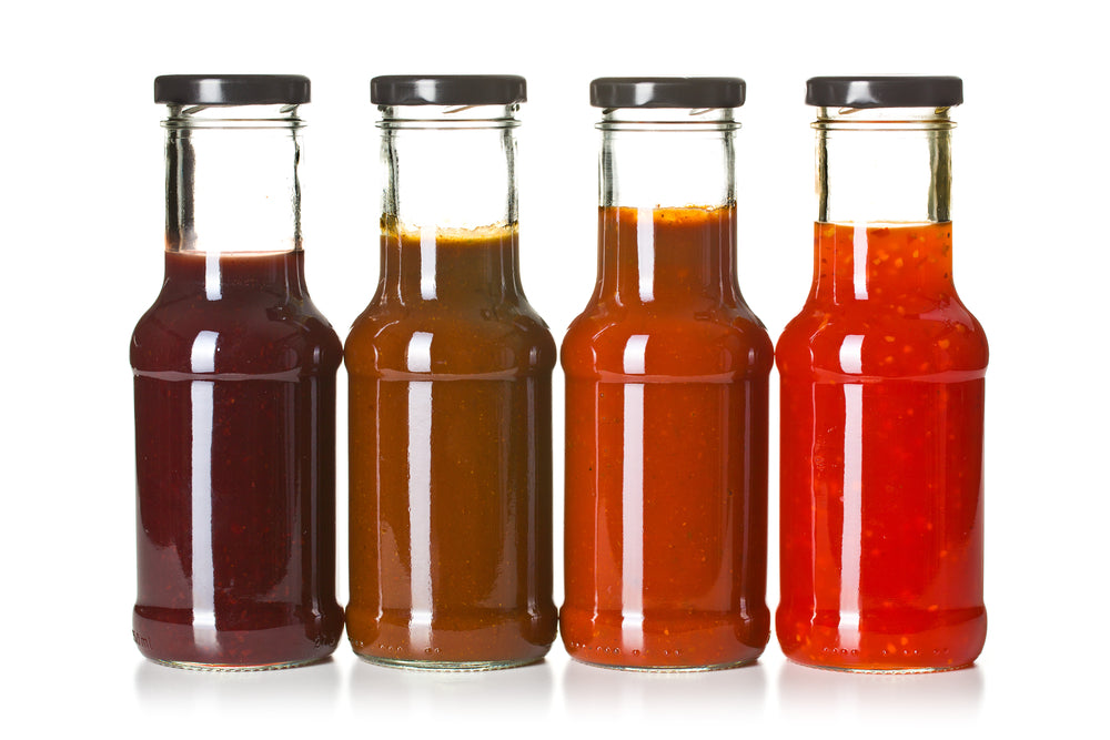 Four glass jars filled with different colored bbq sauces