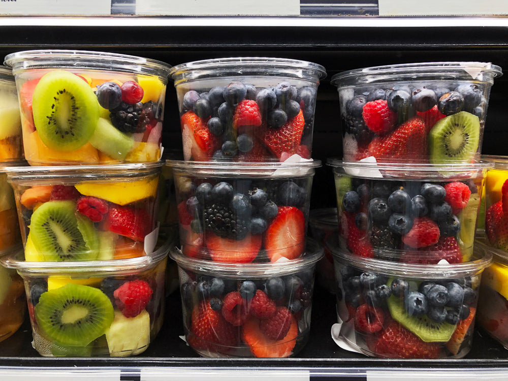 Nine small plastic containers filled with various fruit stacked neatly on the shelf of a fridge
