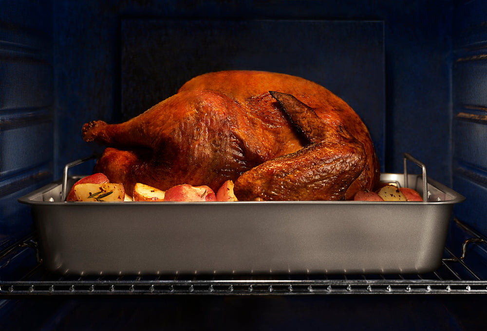 Brown turkey cooking in an oven on a bed of potatoes in a steel tray