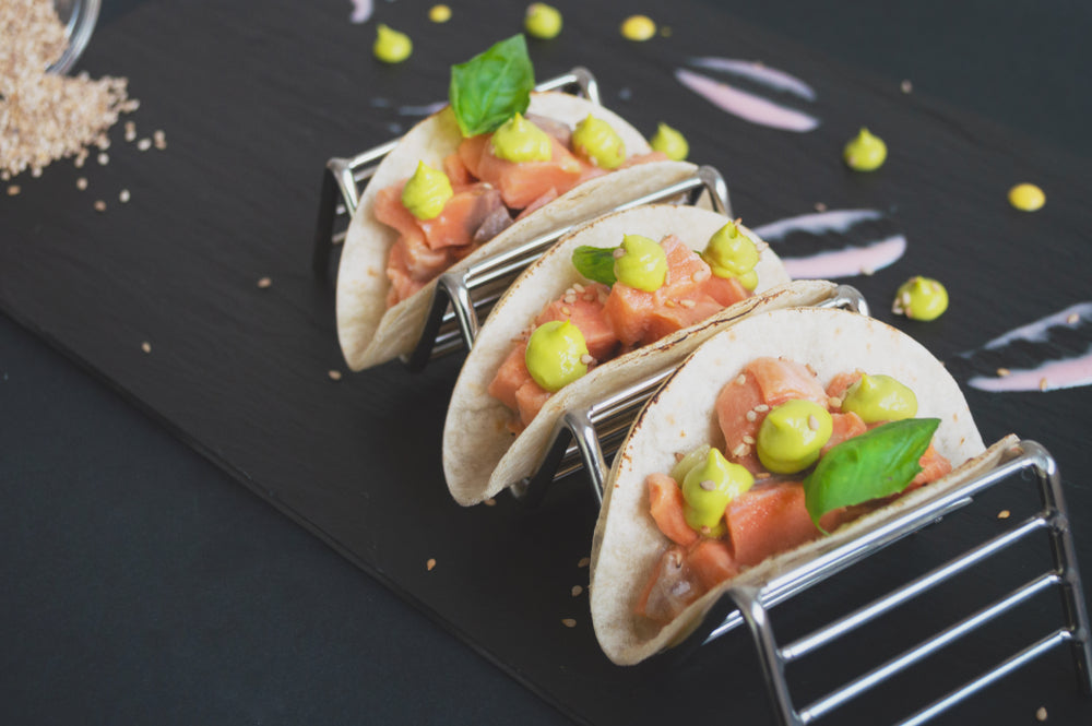 Three salmon and avocado tacos on a metallic taco serving stand
