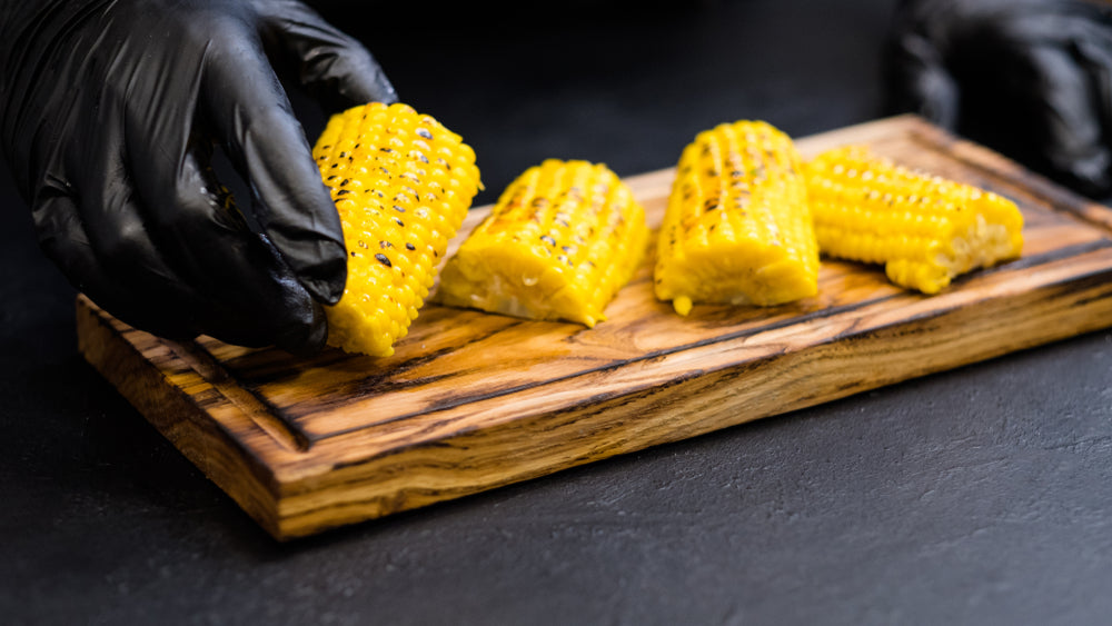 Two hands in black bbq gloves arranging corn on the cob on a small cutting board