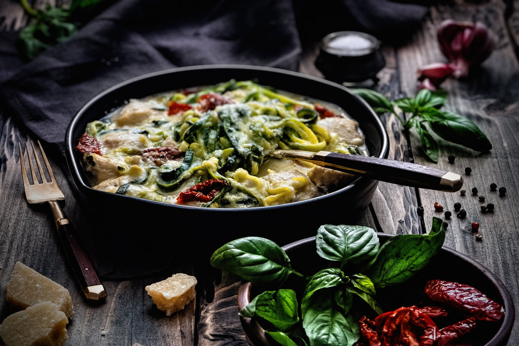 A black bowl filled with pasta covered in parmesan cheese, tomatoes, pesto and Alfredo sauce has a fork balancing on its edge