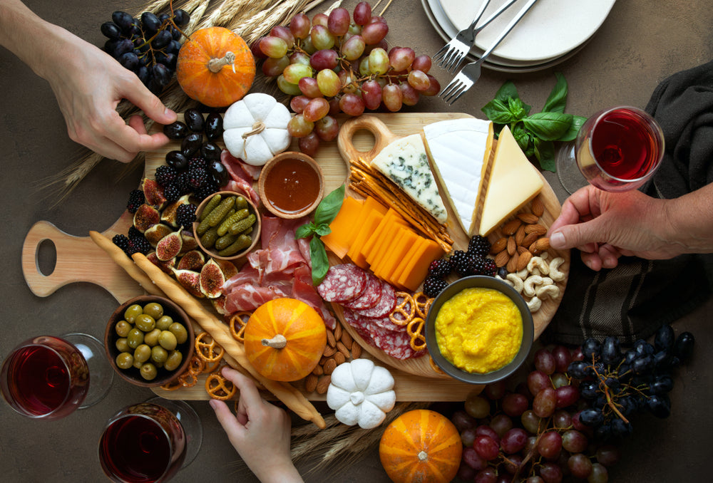 Three people reach for a Charcuterie board filled with different cheese and meats
