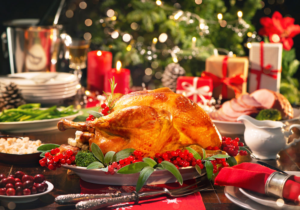 Cooked turkey presented on a Christmas dining table surrounded by side plates of food, candles and gifts