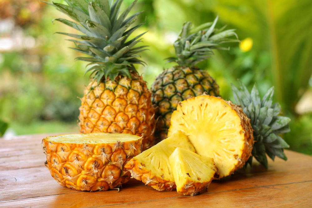 Sliced and half of Pineapple on wooden table with blurred garden background.