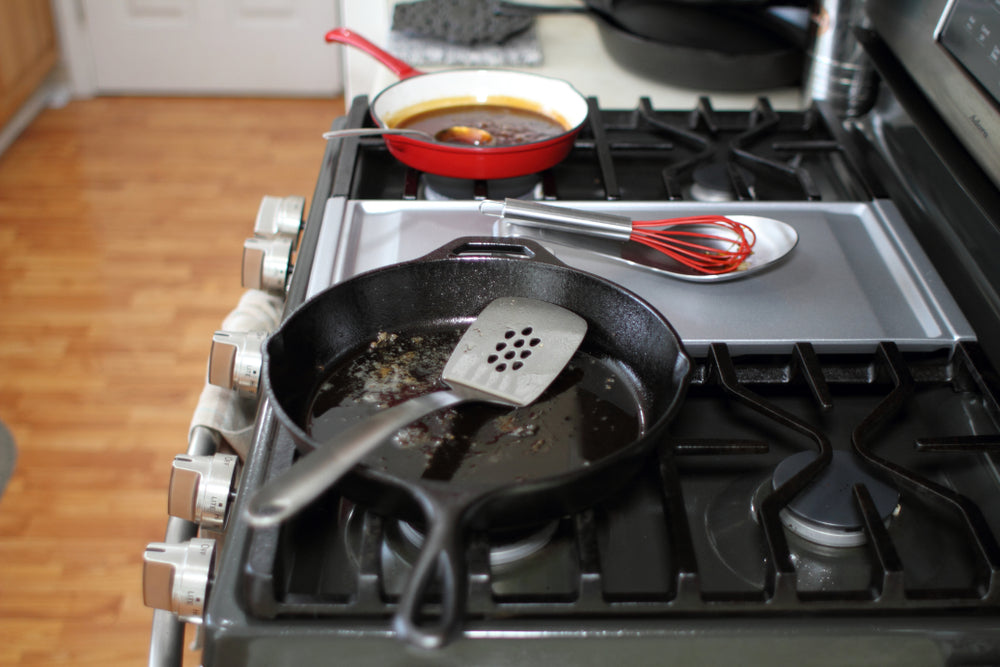 Used skillets resting on the stove top in a kitchen.