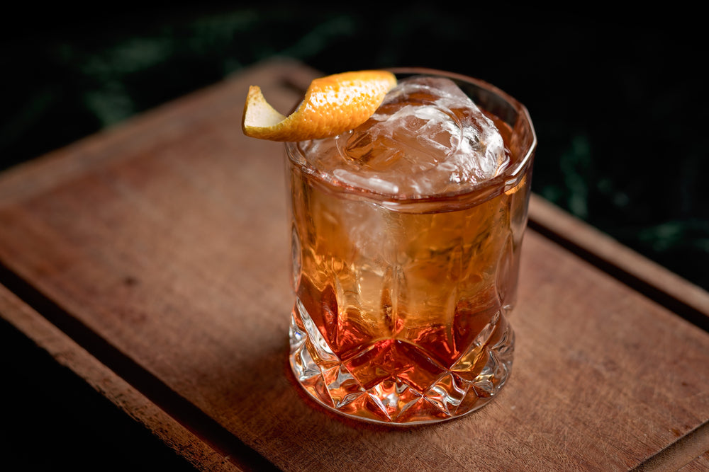 Old fashioned, classic cocktail served on the rocks on a wooden cutting board