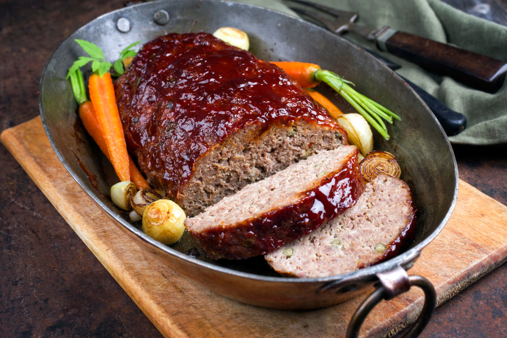Baking tray with meatloaf surrounded by carrots and other vegetables