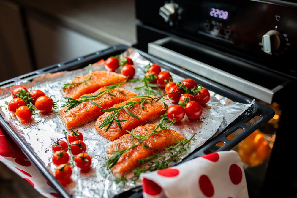A tray of salmon with garnish is being placed into an oven