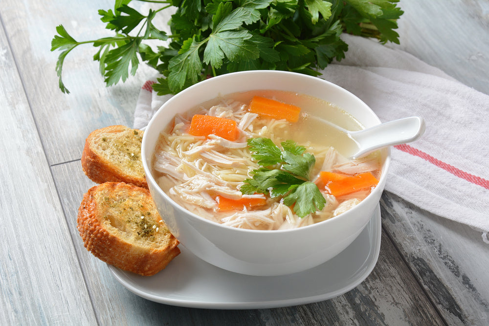 White bowl filled with chicken noodle soup on a white plate with two slices of garlic bread