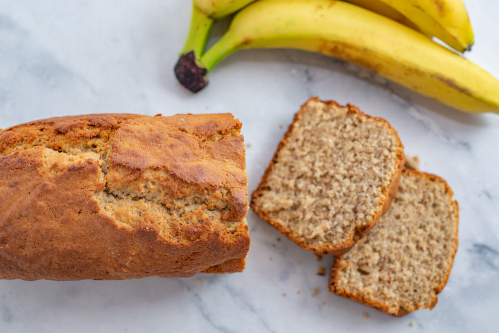 A banana bread loaf on a marble surface with two slices cut from the top beside two bananas