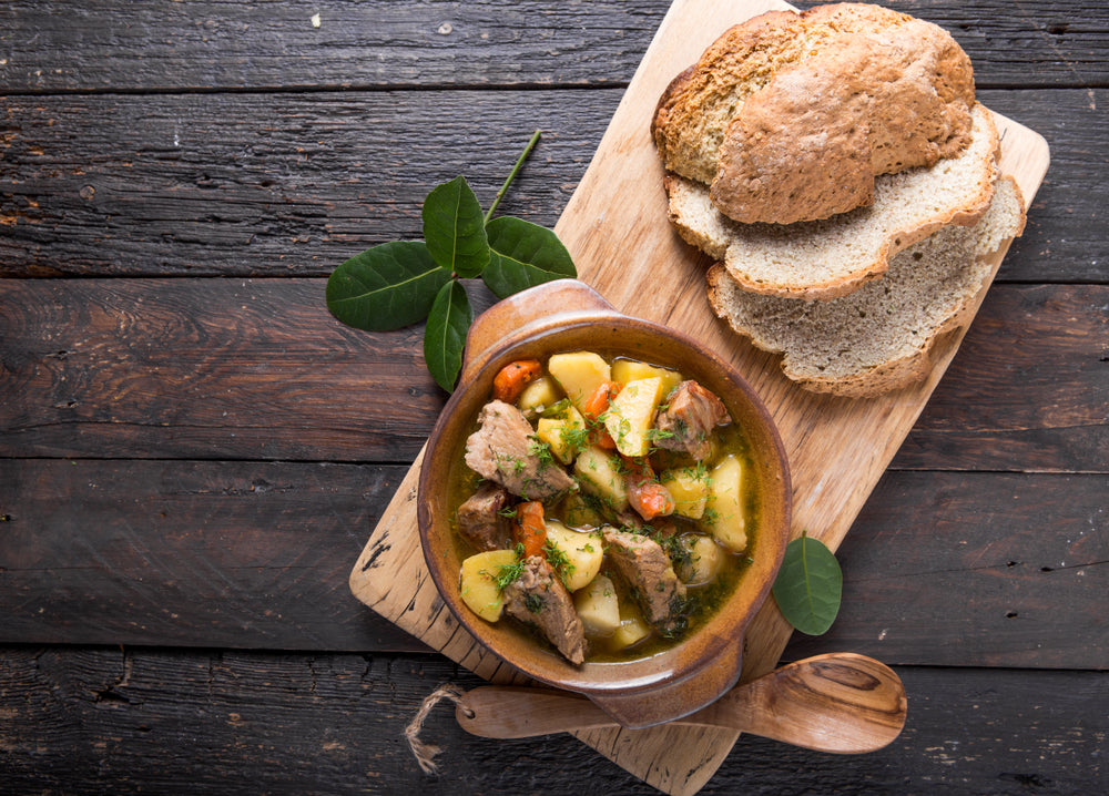 Irish stew in a small bowl next to slices of bread on a wooden cutting board
