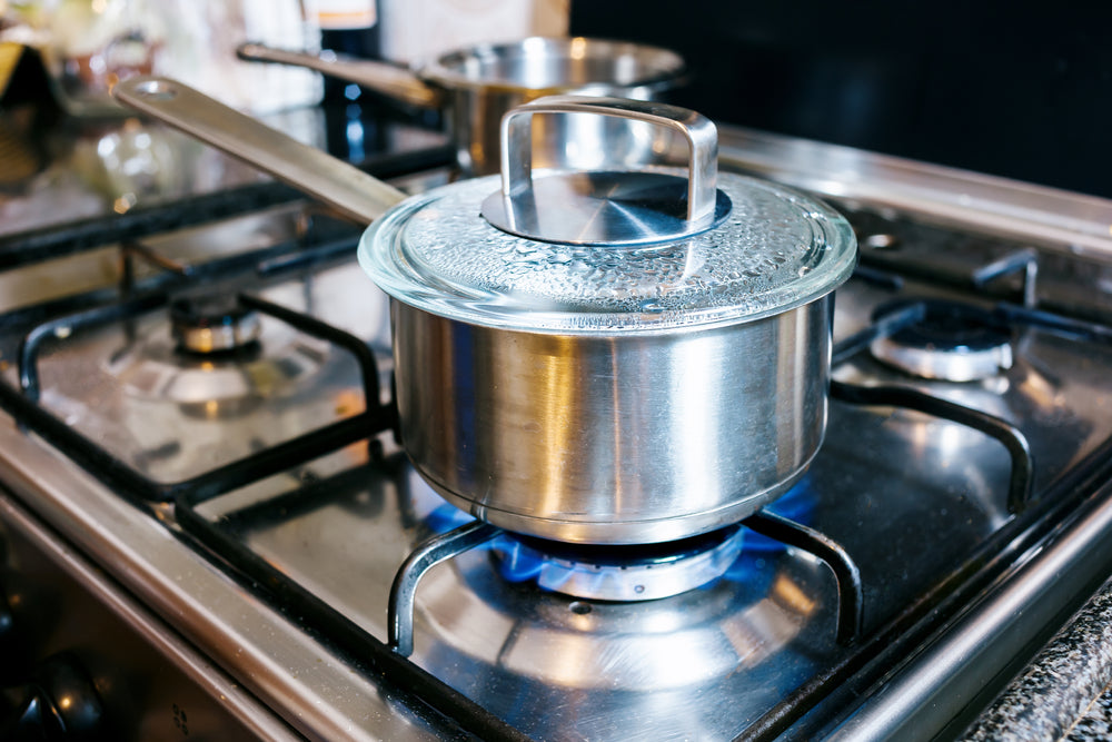 A silver saucepan that is bubbling to the lid on a black kitchen stove