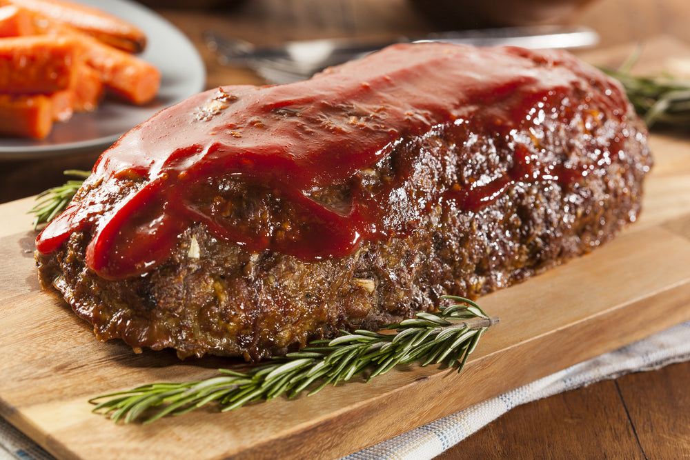 Meatloaf covered in sauce on a brown wooden cutting board with a plate of carrots in the background