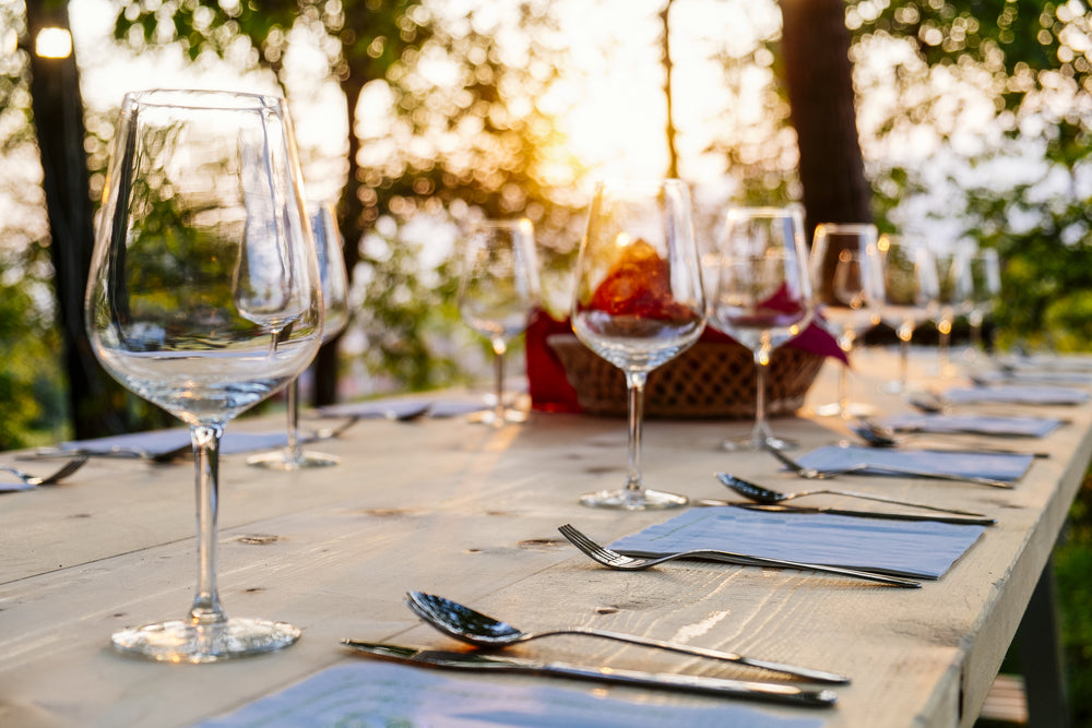 Out door dining table set for dinner with blue place mats, cutlery and wine glasses and a sunset background