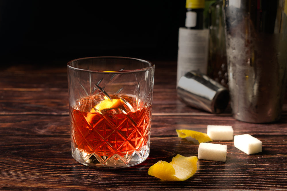 Sazerac cocktail in a old fashioned glass, with a lemon peel, on a dark wooden background.