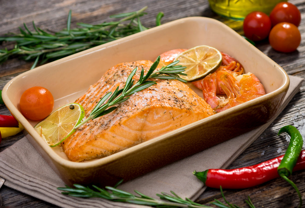 Salmon in a ceramic baking dish with slices of lime and tomatoes as garnish