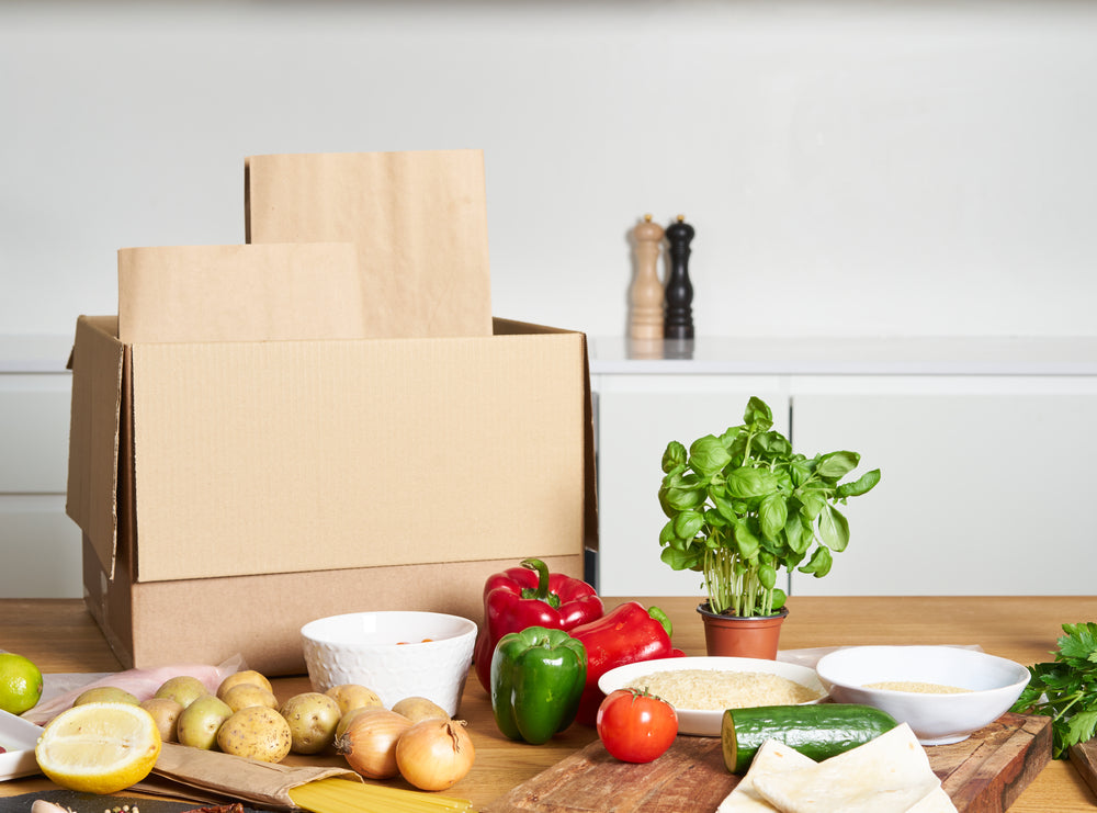 Cardboard box on kitchen counter next to a variety of vegetable ingredients