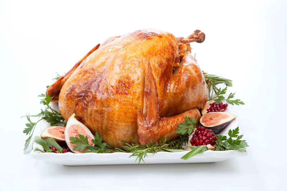 Traditional roasted turkey, garnished with fresh figs, pomegranate, and herbs on white background.