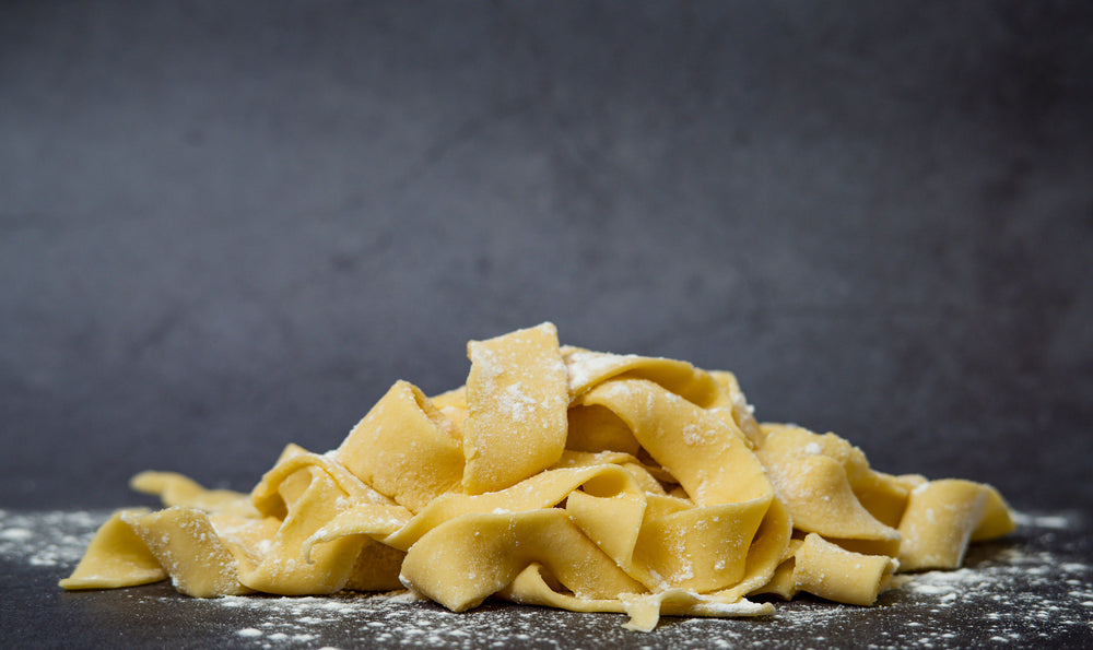 Fresh raw homemade uncooked gluten-free pappardelle pasta on dark table surface with flour on the table, very broad and flat pasta noodles