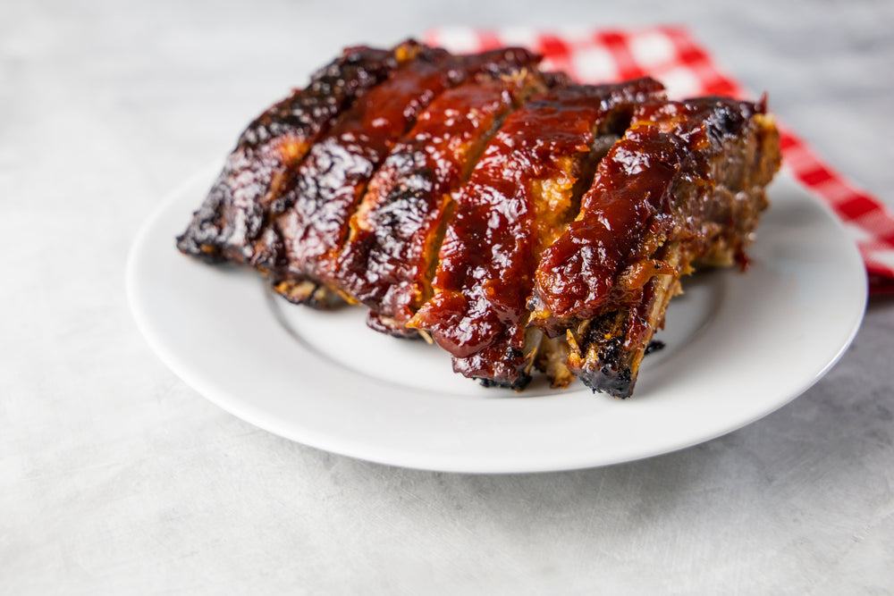 A white plate of bbq ribs marinated in sauce