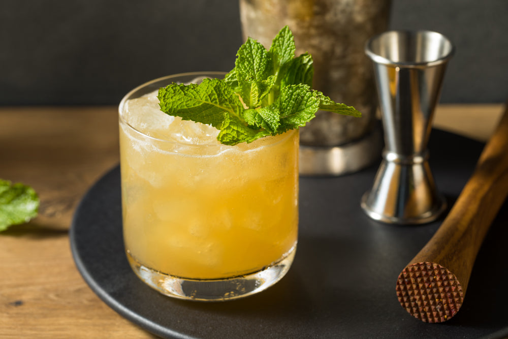 Boozy Refreshing Whiskey Smash with Lemon and Mint on a serving tray