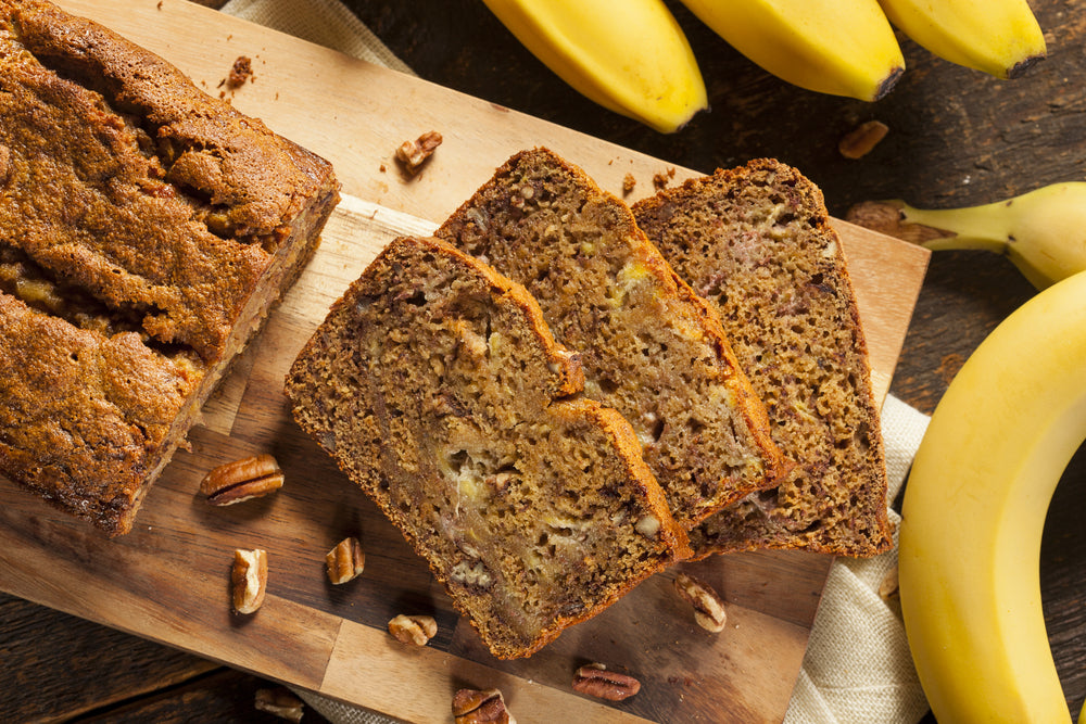 Three slices of banana bread cut from the load on a chopping board next to four bananas