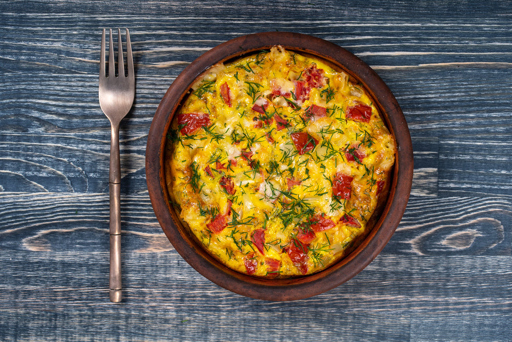 A fork next to a fully intact fresh frittata with basil seasoning