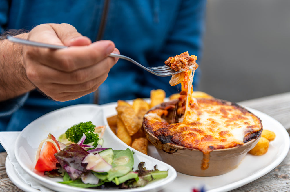 Food on a white plate such as portion of lasagne, chips and salad