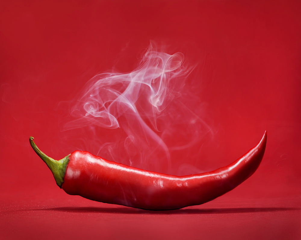 A spicy red pepper against a red background with smoke coming from it
