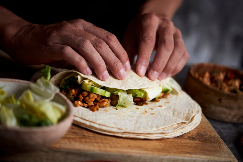 Close up of hands folding meat and vegetables in a tortilla to make a burrito