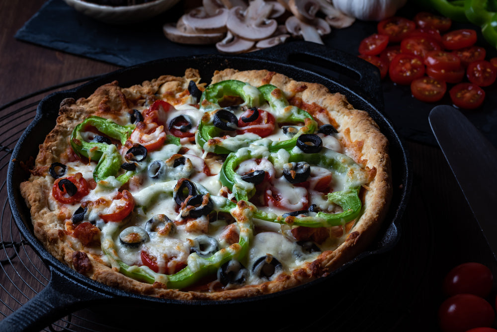 Deluxe Deep Dish Pizza in a black cast iron skillet on a black background