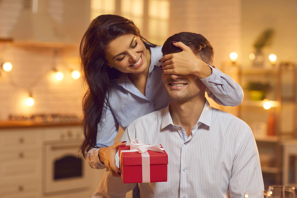 Woman in blue shirt standing in kitchen covers boyfriend's eyes to surprise him with red gift box