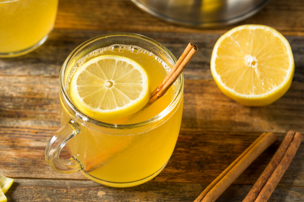 Homemade Hot Toddy Cocktail with Whiskey and Lemon on a wooden surface