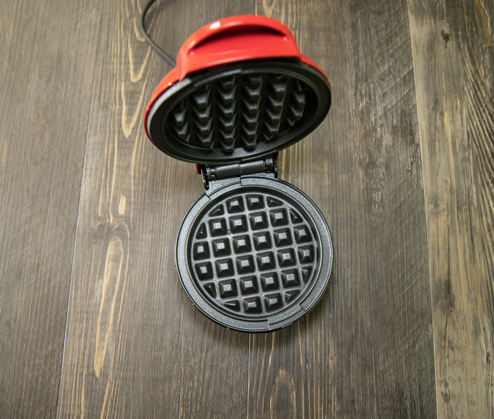 A red waffle iron on a wooden floor