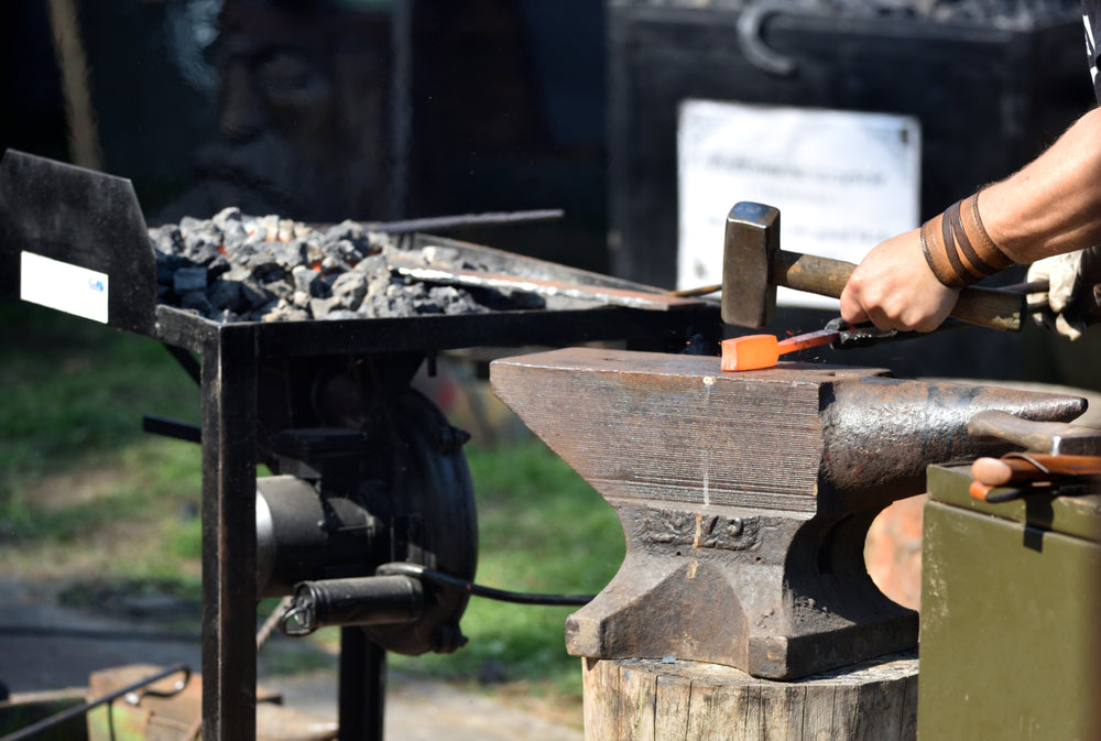 Man forges damascus steel by hand outdoors