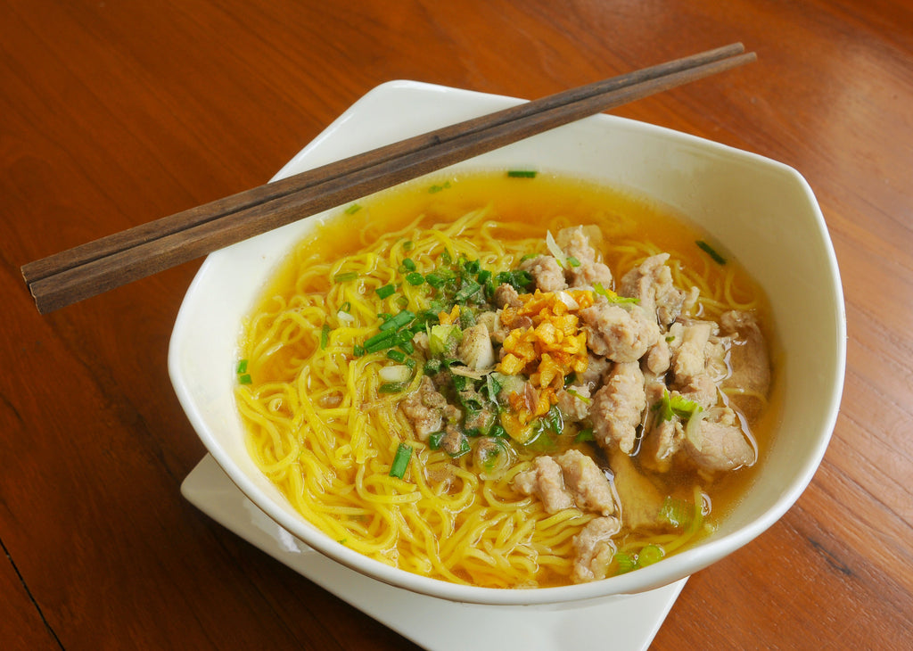 Large white bowl of chicken noodle soup with two chop sticks resting on the edge