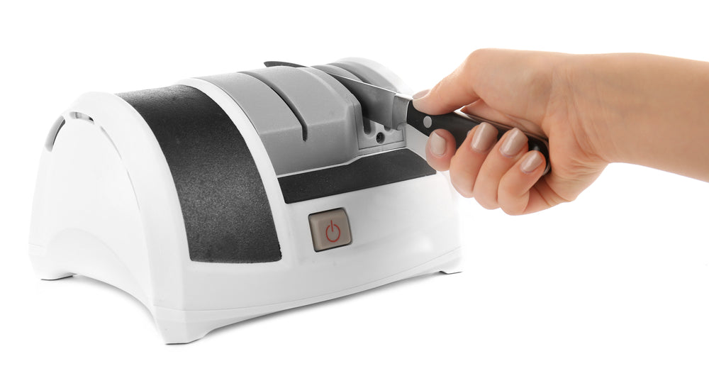 A hand placing a knife through an electric knife sharpener with a white background