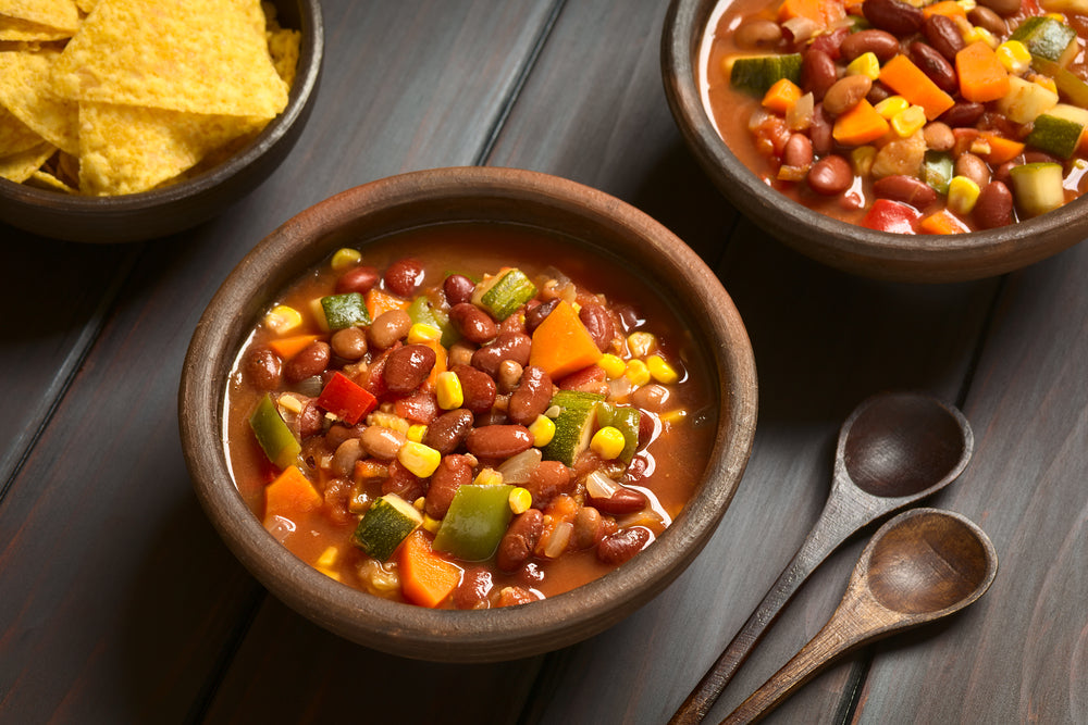 Bowl of vegetarian chili with beans and vegetables next to two dark wooden spoons