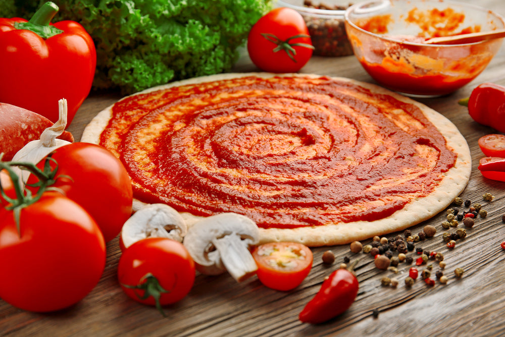 Uncooked pizza dough with tomato sauce spread across it surrounded by fresh tomatoes and diced mushrooms