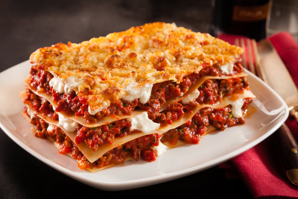 Slice of lasagne with three layers of cheese on a white plate