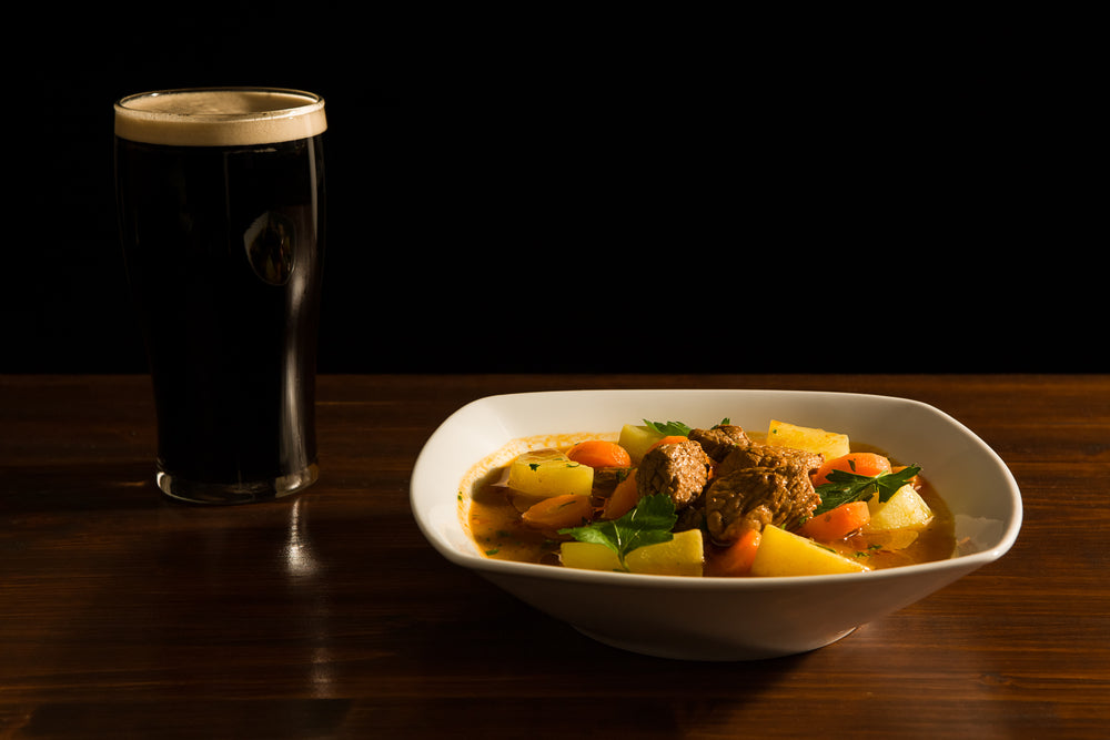 Pint glass of dark beer with white head next to a bowl of traditional Irish beef stew