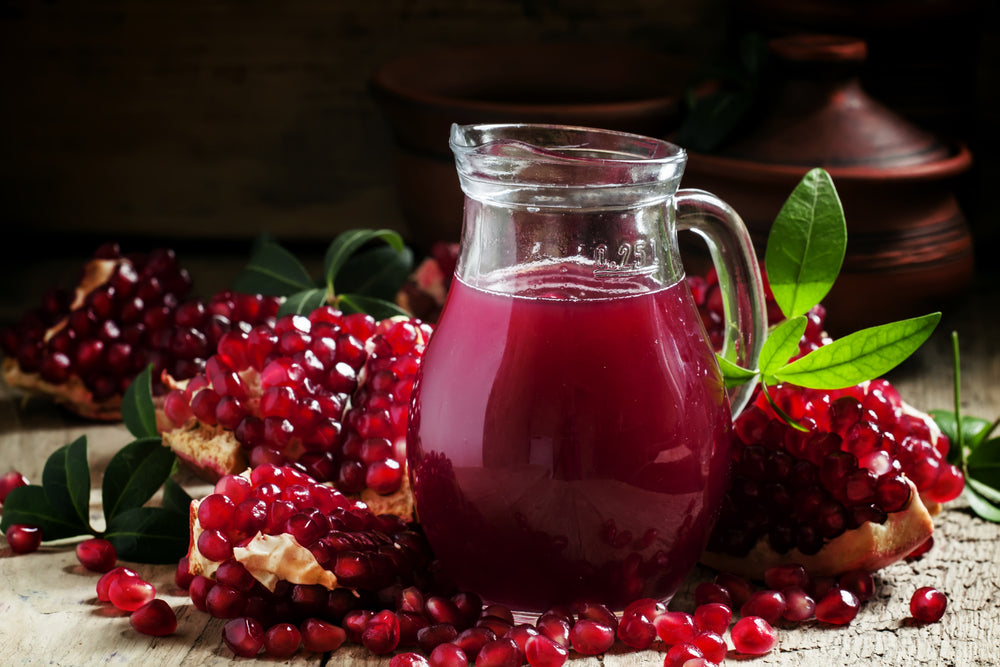 Jug with fresh pomegranate juice on the background of open grenade on dark wooden background