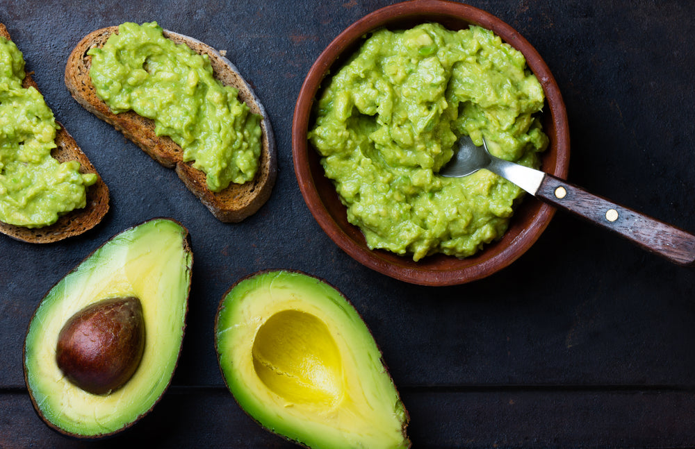 A bowl of guacamole next to chopped avocados and bread with guacamole topping