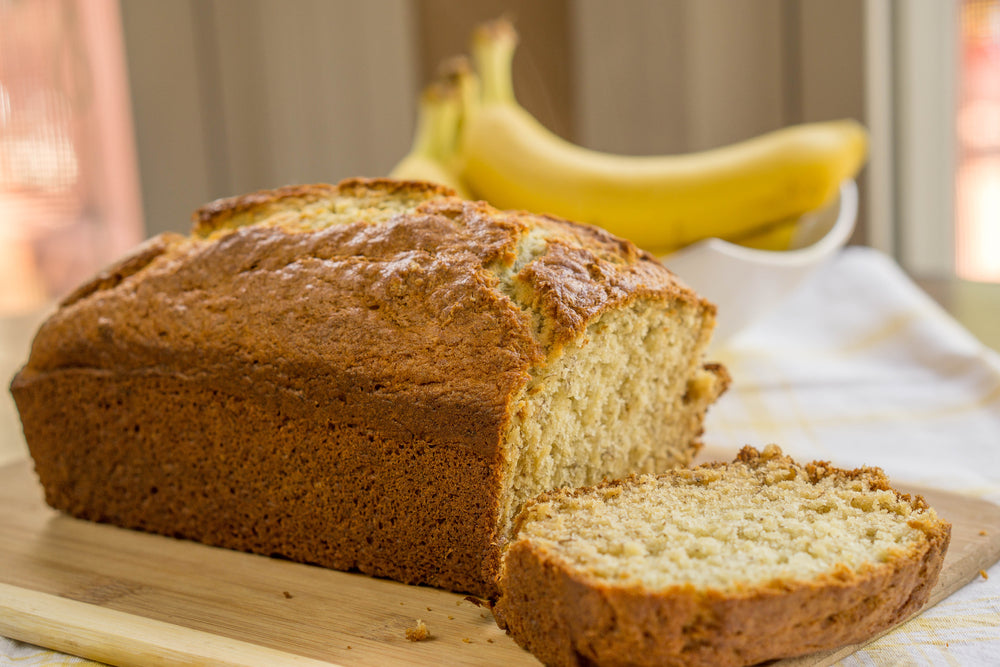 Banana Bread Loaf on a cutting board with bananas in the background