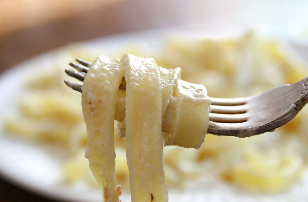 Pasta covered in alfredo sauce wrapped around a silver fork with a blurred plate of past a in the background
