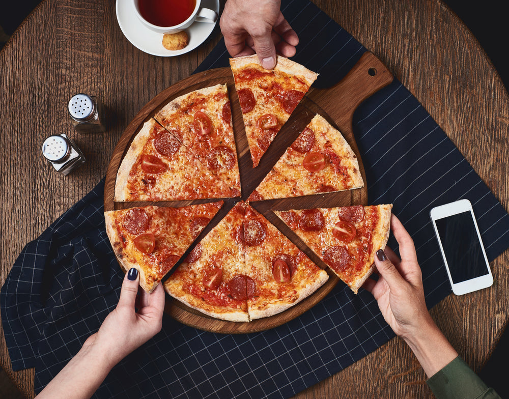Three people reaching for different slices of a pizza on a circular cutting board