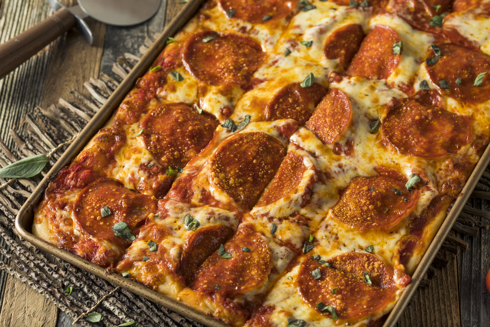 Homemade Sicilian Style Pizza with pepperoni still in the baking tray on a kitchen table